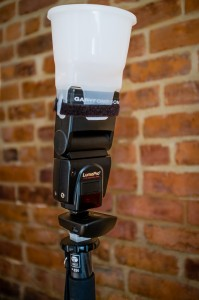 Flash mounted on a monopod, with radio trigger and plastic diffuser.